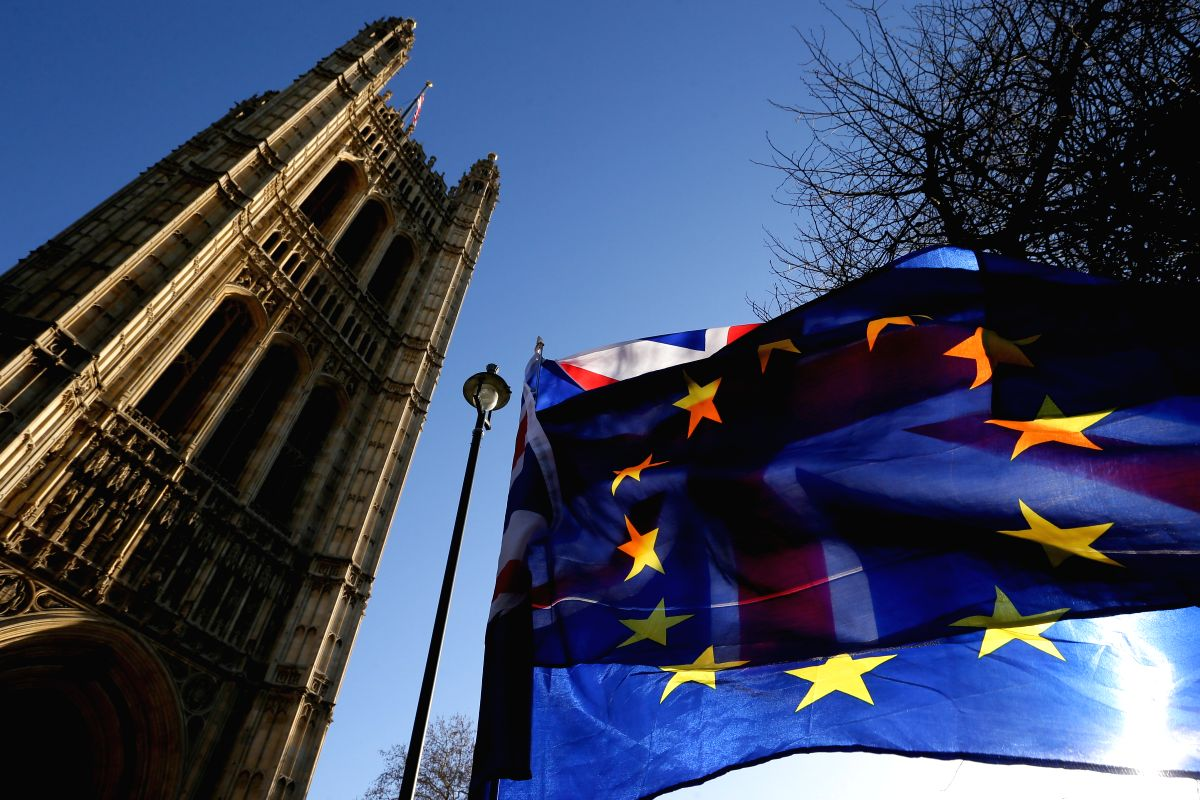 LONDON, Jan. 17, 2019 (Xinhua) -- An EU flag is seen in front of a UK flag outside the Houses of Parliament in London, Britain, on Jan. 17, 2019. Leading economists have warned that the British economy could suffer if the country leaves the European