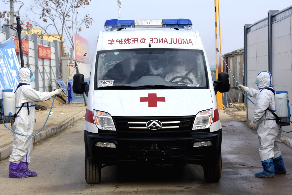Medical staff disinfect an ambulance carrying cured patients at Huoshenshan (Fire God Mountain) Hospital in Wuhan, central China's Hubei Province, Feb. 13, 2020. Huoshenshan Hospital, a makeshift hospital built in Wuhan amid the novel coronavirus pne