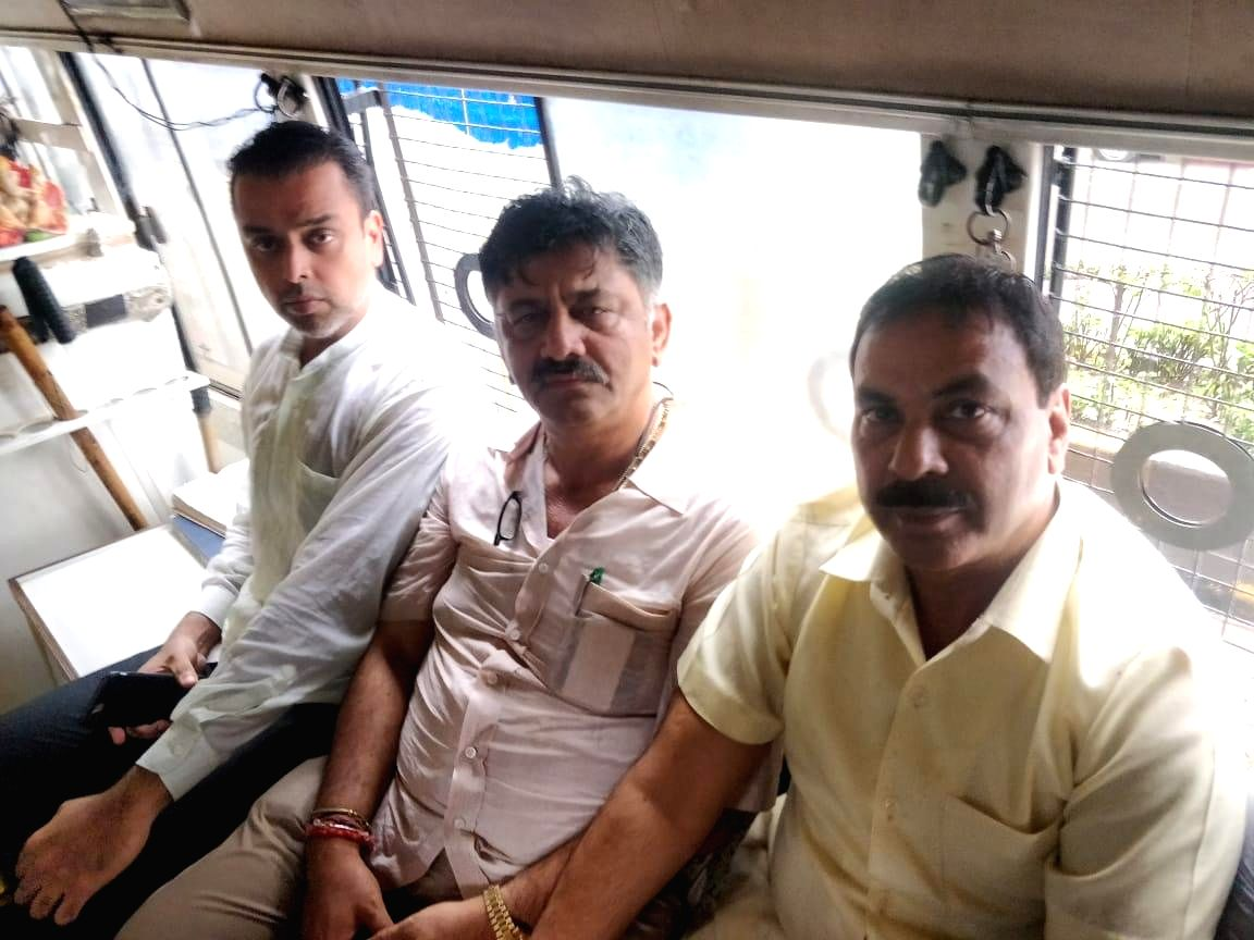 Mumbai: Congress leaders D.K. Shivakumar and Milind Deora in a police van after being detained outside the five-star hotel, where the Karnataka rebel MLAs are holed up in Mumbai, on July 10, 2019.