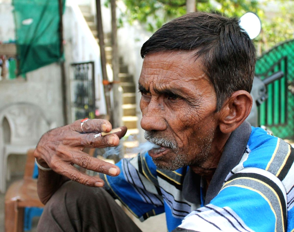 Nagpur: A man smokes a bidi - cigarette made of unprocessed tobacco wrapped in leaves - at a roadside in Nagpur on May 31, 2018. May 31 is observed as 'World No Tobacco Day' worldwide.