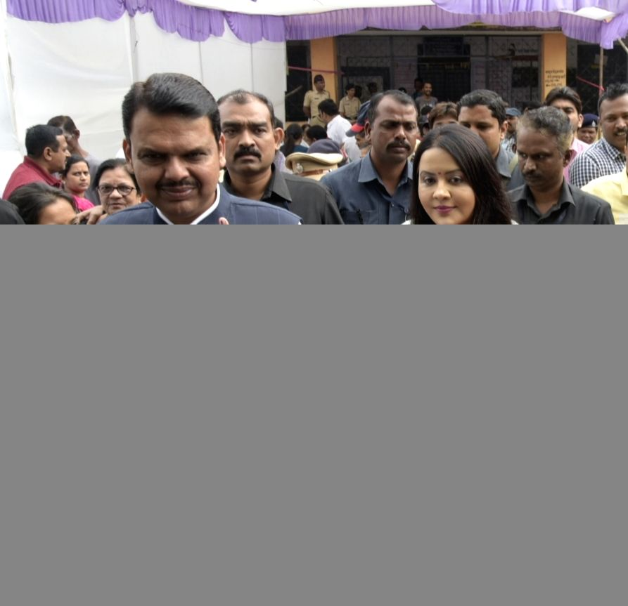 Nagpur: Maharashtra Chief Minister Devendra Fadnavis and his wife Amruta Fadnavis show their her inked fingers after casting their votes for Maharashtra Assembly elections, in Nagpur on Oct 21, 2019.