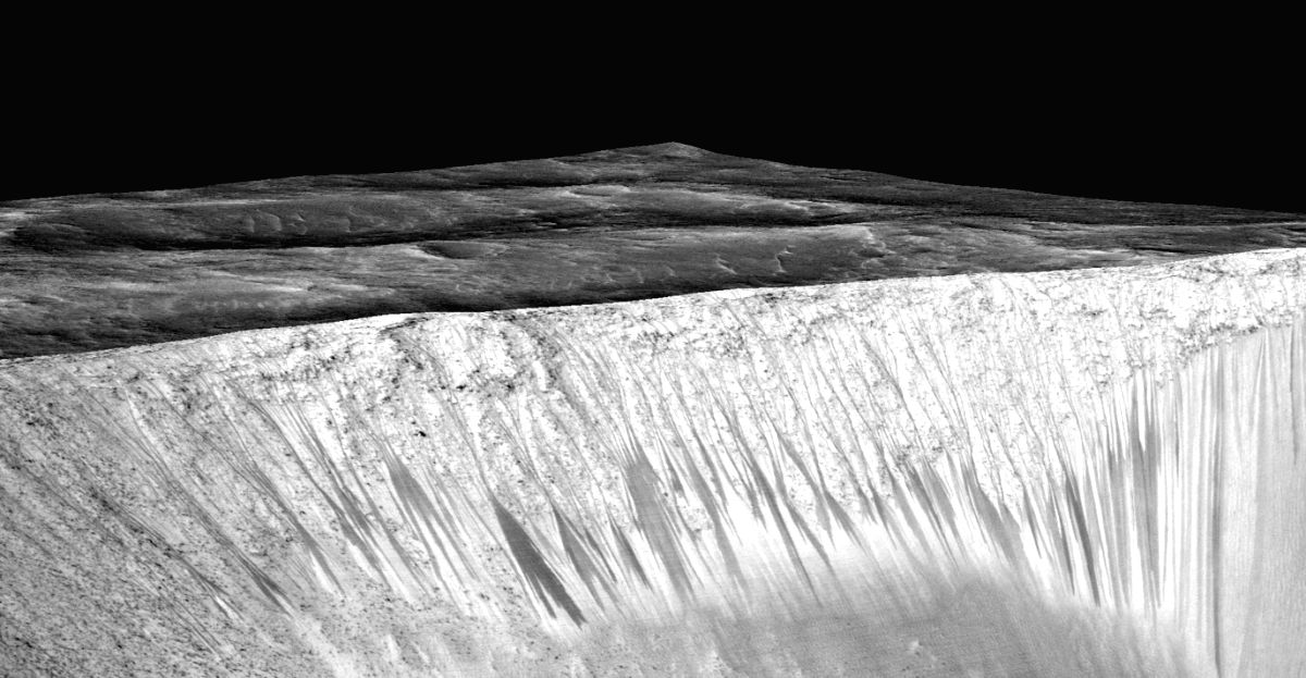 NASA: Dark narrow streaks called recurring slope lineae emanating out of the walls of Garni crater on Mars. The dark streaks here are up to few hundred meters in length. They are hypothesized to be formed by flow of briny liquid water on Mars. (Photo
