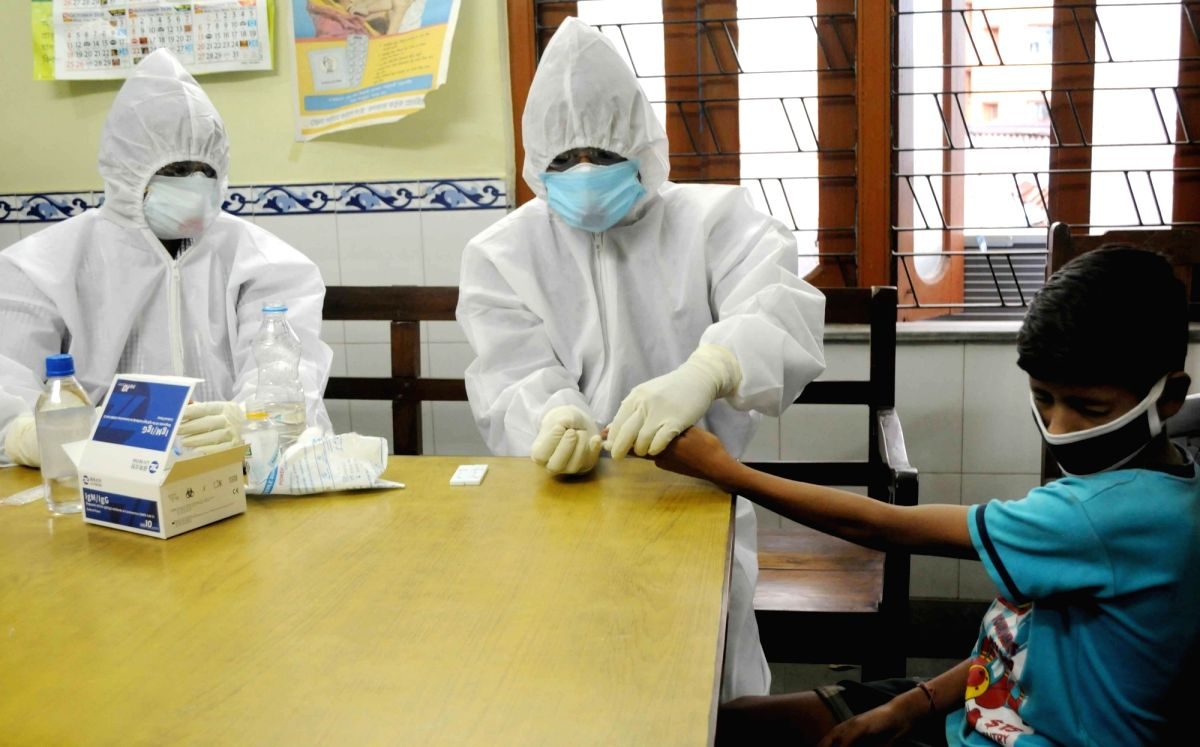 New Delhi: A health worker wearing a Personal Protective Equipment (PPE) suit collects blod sample from a person at a testing center in Kolkata during the extended nationwide lockdown imposed to mitigate the spread of coronavirus; on Apr 21, 2020. (P