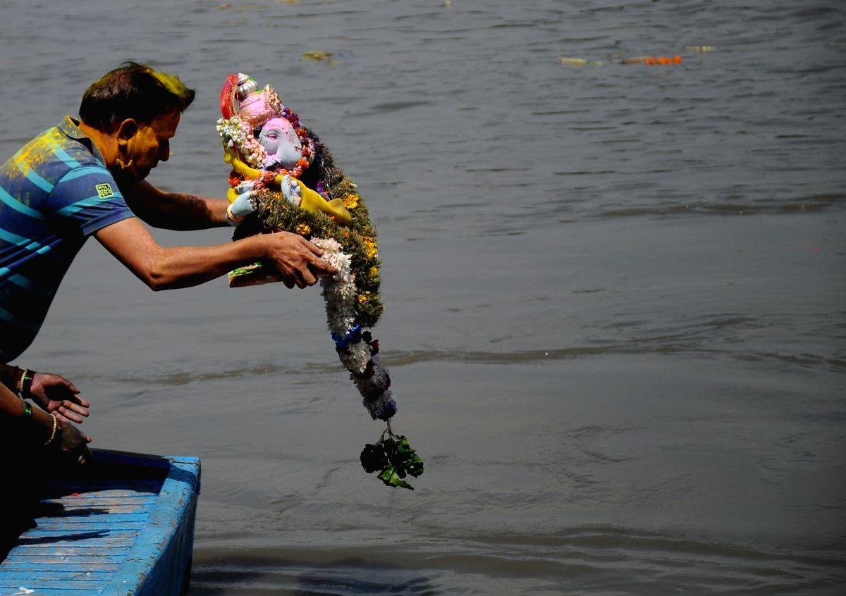 New Delhi: Devotees immerse Idol of Goddess Ganesha at river Yamuna in New Delhi on Sunday, September 19, 2021. (Photo: Qamar Sibtain/IANS)