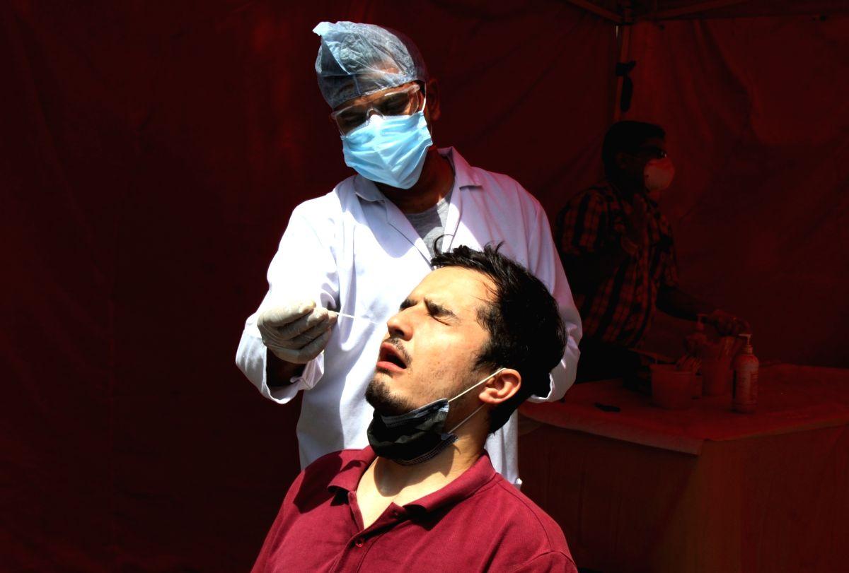 New Delhi: Health worker collect swab sample for Covid-19 testing at South MCD Dispensary Jangpura in New Delhi on Tuesday April 27, 2021.(Photo: Wasim Sarvar/IANS)