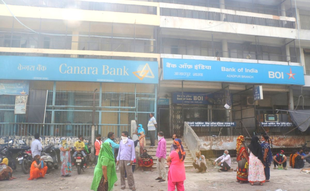 New Delhi: People wait for Canara Bank to open during the extended nationwide lockdown imposed to mitigate the spread of COVID-19 pandemic, in New Delhi on Apr 15, 2020.