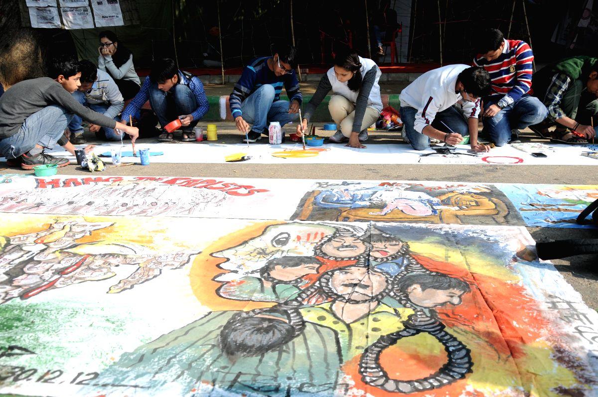 New Delhi: Social activists paint pictures to condemn 2012 Nirbhaya gangrape the  at Jantar Mantar in New Delhi on Dec 16, 2014.