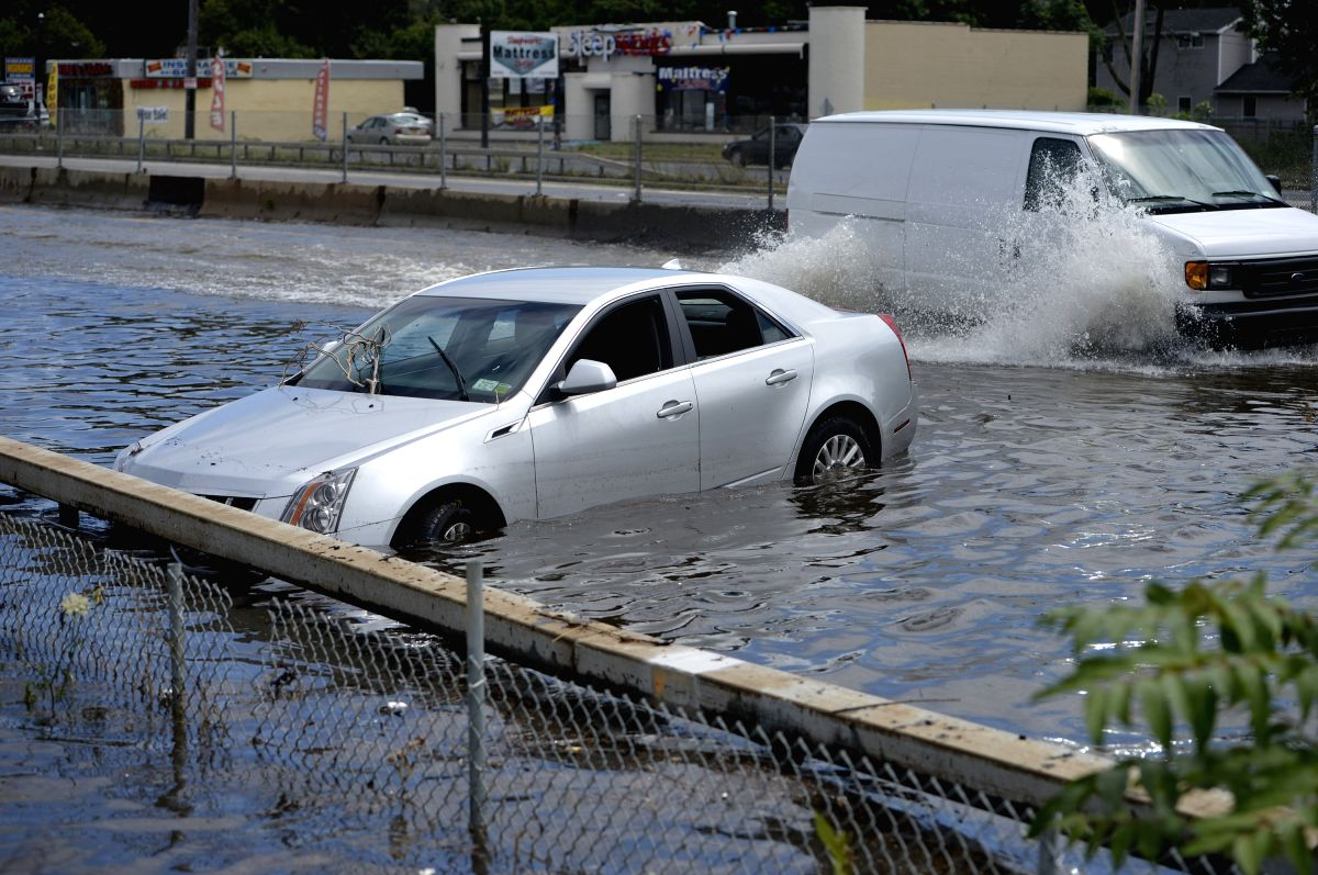 NEW YORK, Aug. 13, 2014 (Xinhua) --  A car is abandoned on a flooded road following heavy rains and flash flooding in Bay Shore in New York, the United States, on Aug. 13, 2014. A rain storm saturated the New York City area for 10 hours on Wednesday
