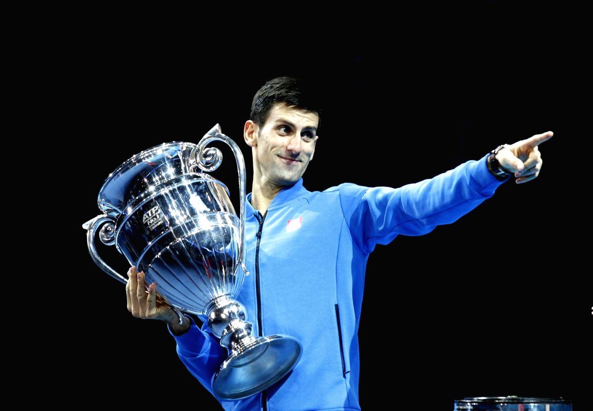 :Novak Djokovic of Serbia celebrates while holding the ATP World No. 1 Award trophy following his men's singles group stage match against Kei Nishikori of ...