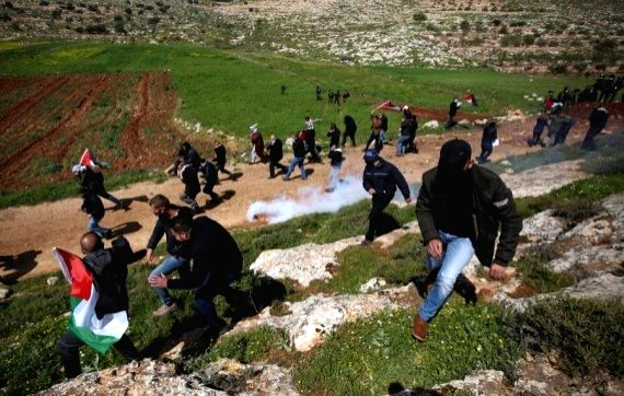 Palestinian protesters run to take cover from tear gas fired by Israeli security forces during a Palestinian protest against the expansion of Jewish settlements in the West Bank village of Beit Dajan, east of Nablus, March 12, 2021. (Photo by Ayman N