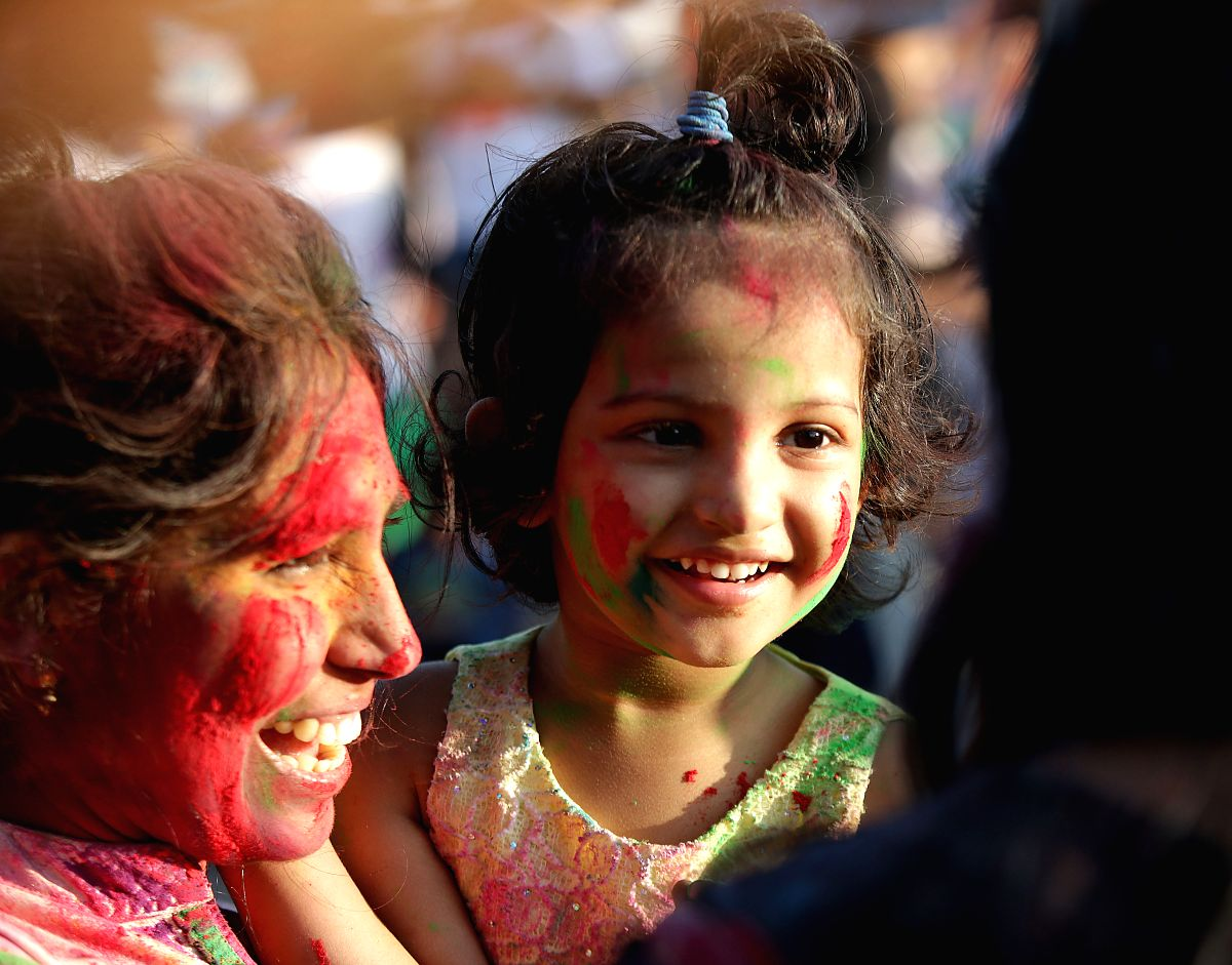 A mother carries her daughter with colored powder