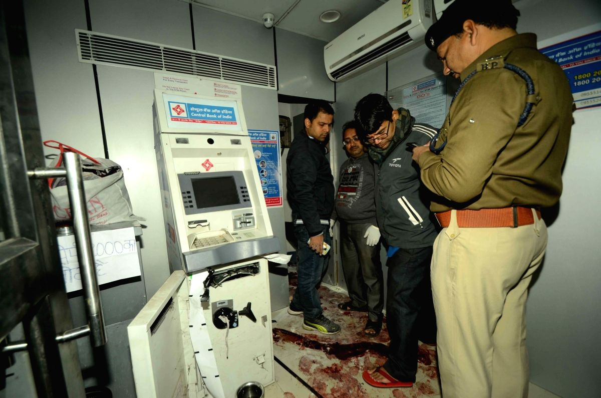 Patna: Patna: Police personnel inspects a crime scene and collects material evidence where Deepak Kumar, the security guard of a Central Bank ATM booth was killed by unidentified people in Patna on Dec 10, 2016.