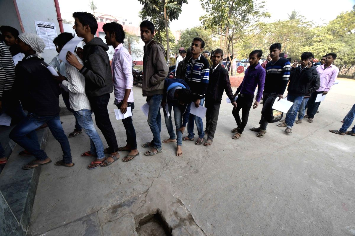 Patna: Students wearing sandals enter an exam centre to appear for higher secondary exams conducted by Bihar School Examination Board (BSEB) as they are barred from wearing shoes, in Patna on Feb 6, 2019.