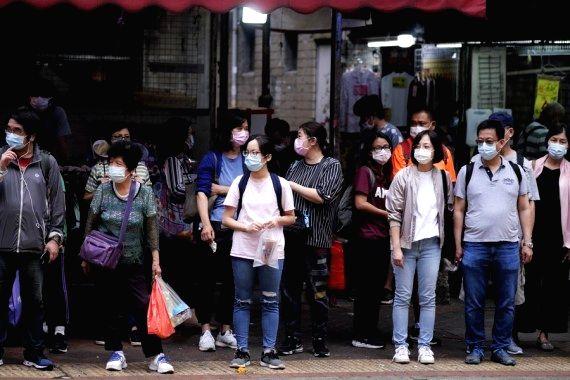 Pedestrians wearing face masks wait to cross a road in Hung Hom, Hong Kong, south China, Nov. 21, 2020. (Xinhua/Wang Shen)