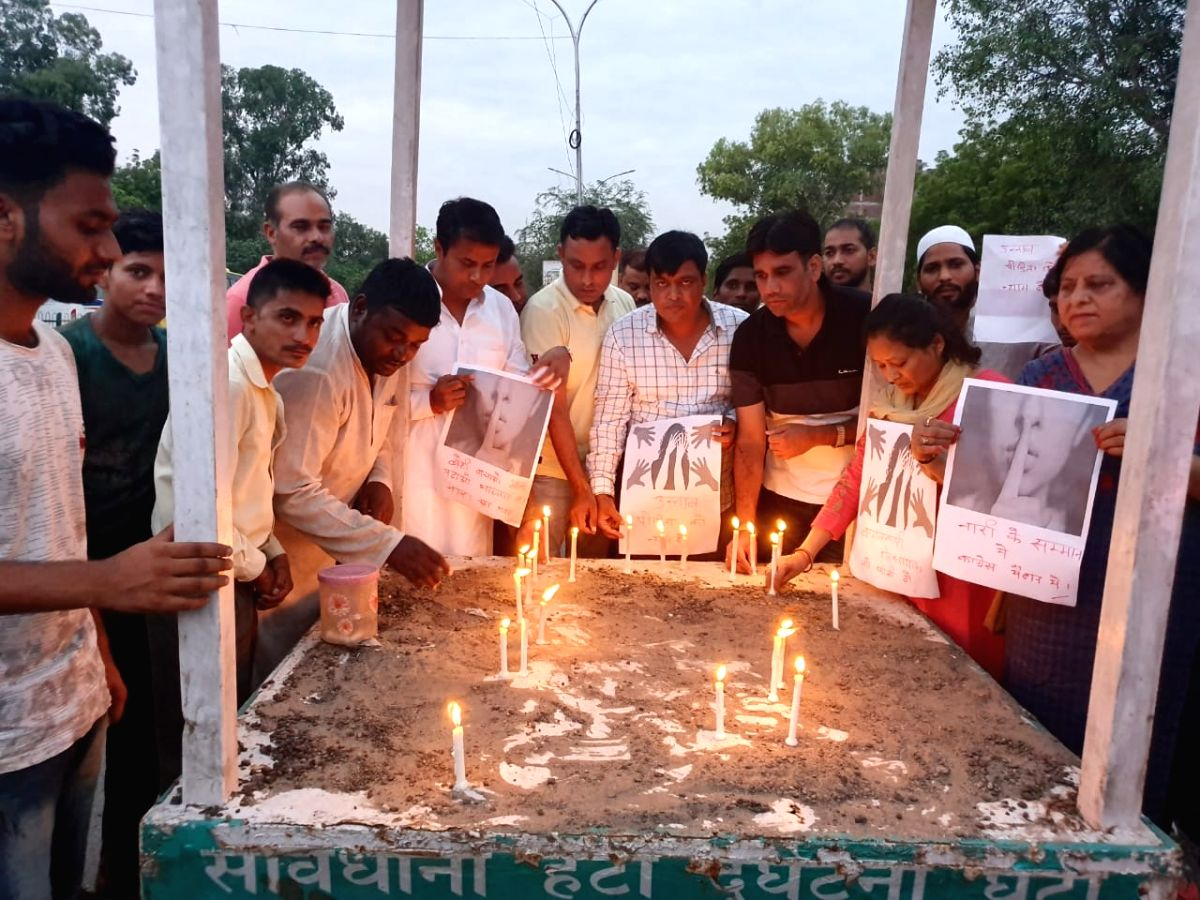 People participate in a candle light protest demanding justice for Unnao rape victim