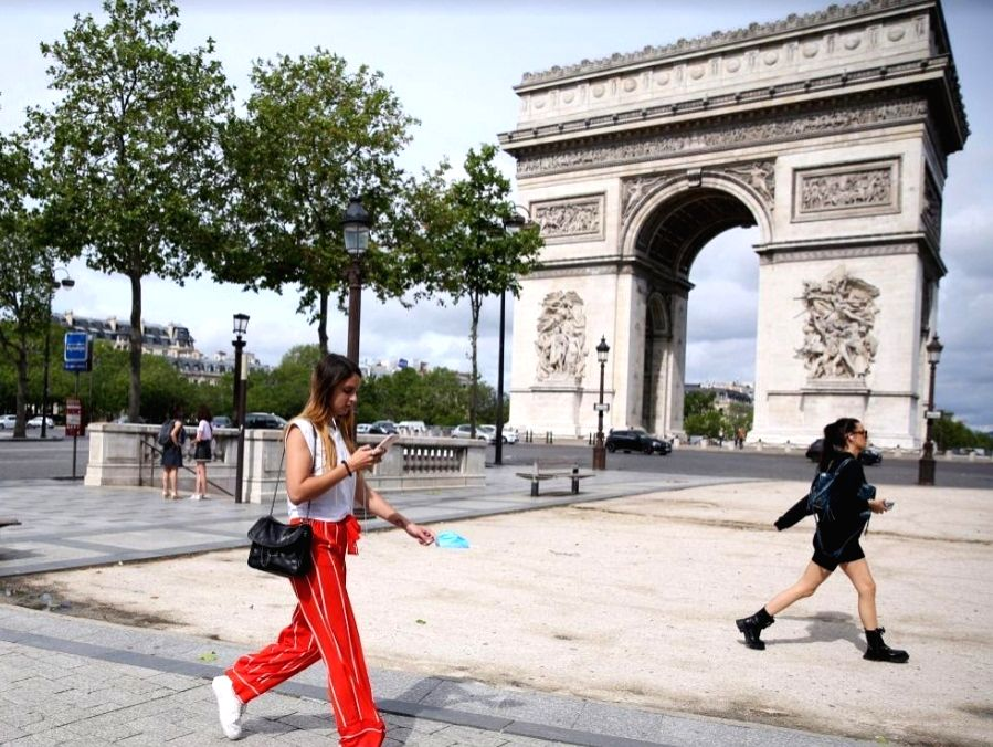 People walk near the Arc de Triomphe in Paris, France, June 17, 2021. French Prime Minister Jean Castex on Wednesday announced that people could stop wearing face masks outdoors starting from Thursday and the night-time curfew will also be lifted sta