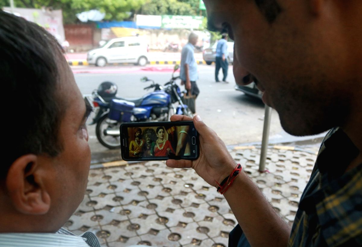People watching video on cell phone. (File Photo: IANS)