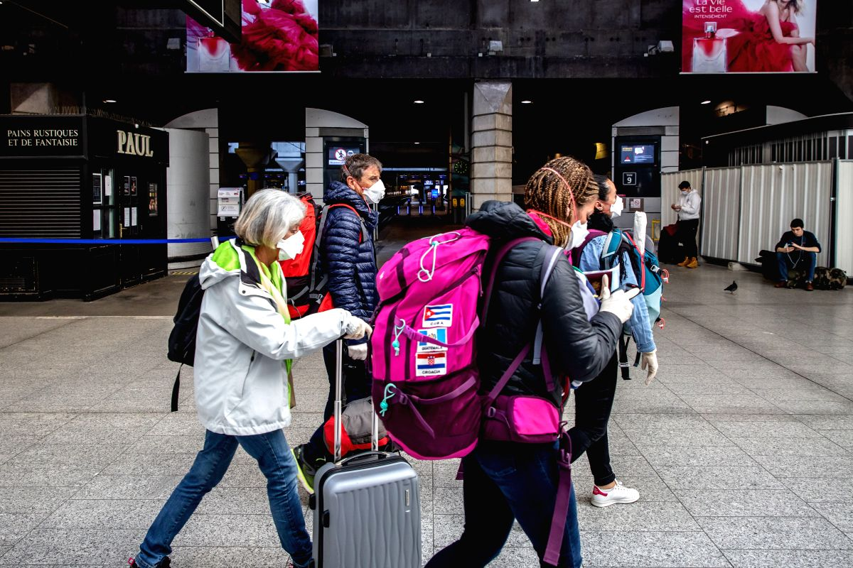 People wearing masks arrive at the Montparnasse train station in Paris
