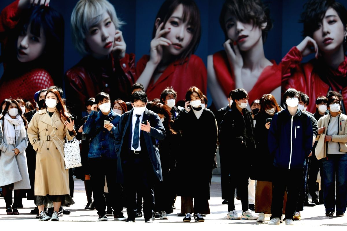 People wearing masks cross the famous scramble intersection near Shibuya Station in Tokyo on March 11. The Japanese government will lift the coronavirus state of emergency for Summer Olympics host city Tokyo on Sunday as planned, despite concerns abo