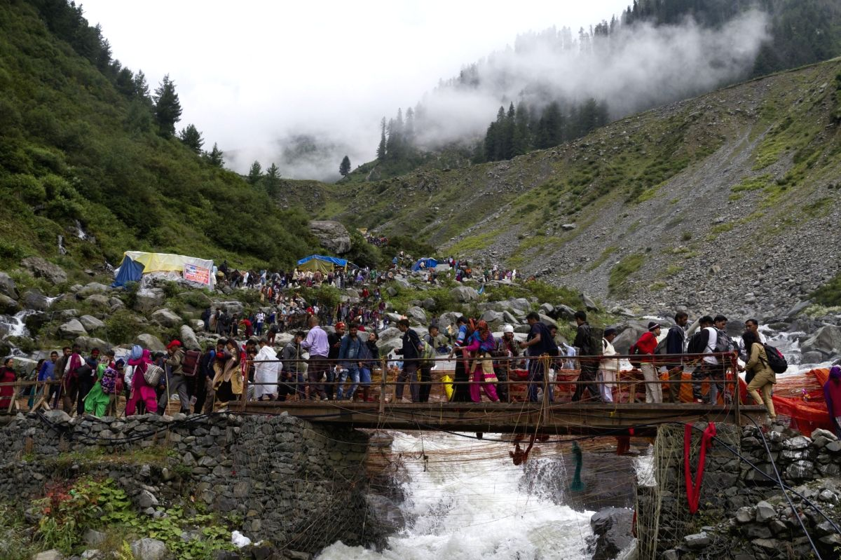 Pilgrims walk through a wooden bridge over Manimahesh Lake near Manimahesh Kailash Peak in the Pir Panjal Range of the Himalaya during Manimahesh Kailash Peak yatra, in Himachal Pradesh's Chamba