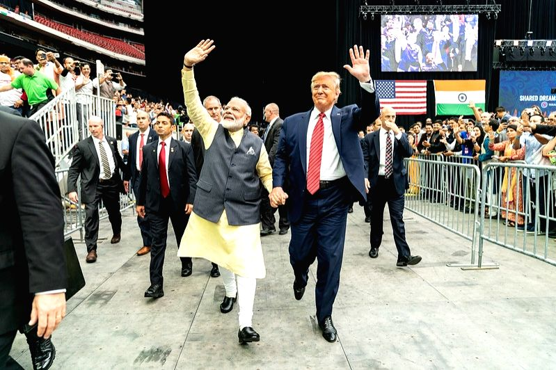 Prime Minister Narendra Modi and President Donald Trump stride around the Houston arena hand-in-hand on September 22, 2019, at the Howdy Modi event, a symbol of growing India-US ties. (Photo: White House/IANS).