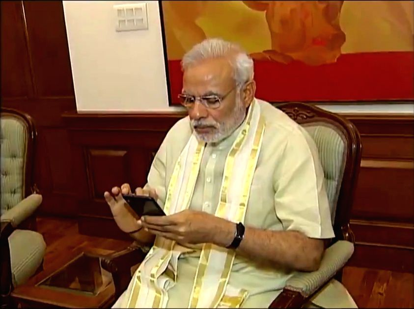 Prime Minister Narendra Modi busy working on his mobile phone.
