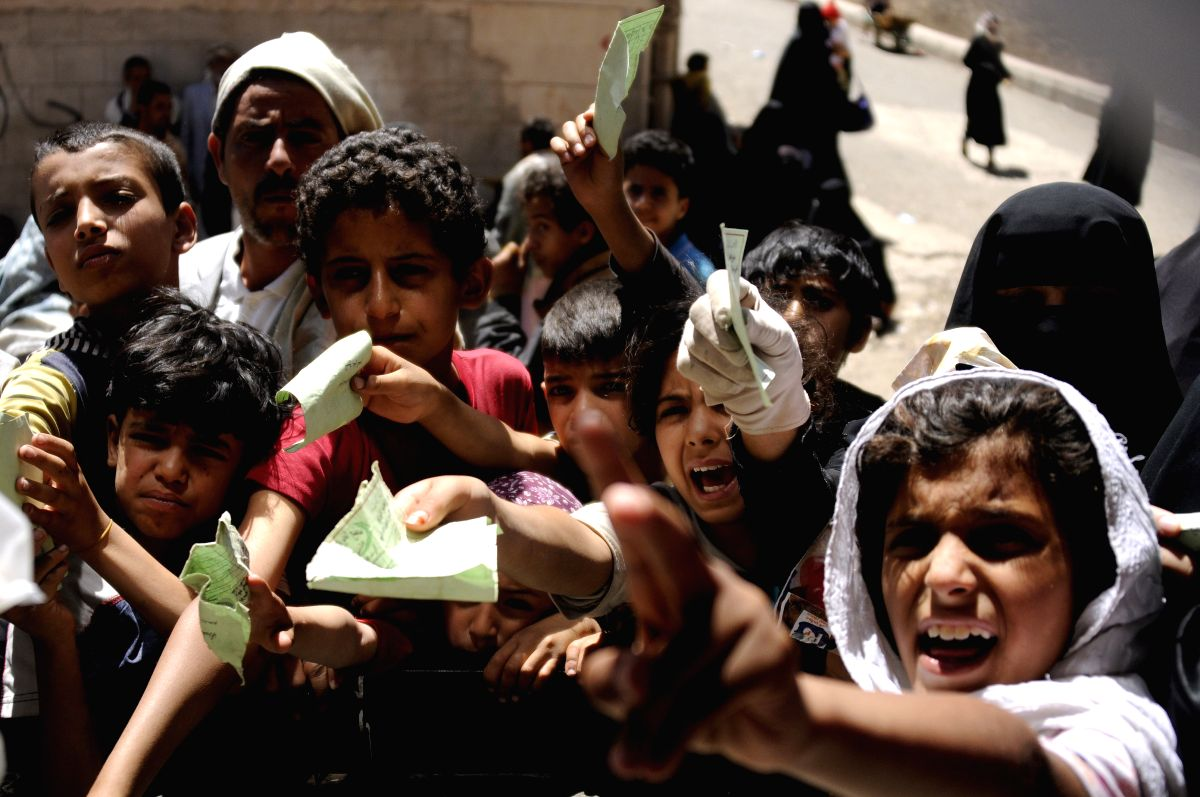 SANAA, April 13, 2017 (Xinhua) -- Children gather to receive food from a helping center in Sanaa, Yemen, on April 13, 2017. The World Food Programme (WFP) is scaling up its emergency food operations in Yemen to provide food assistance to up to 9 mill