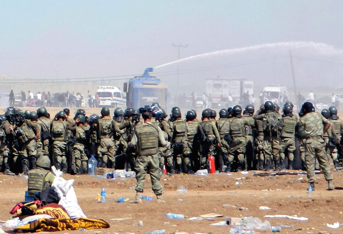 SANLIURFA, Sept. 22, 2014 (Xinhua) -- Turkish police use tear gas and water cannons to prevent people supporting Kurdish resistance of the terrorist Islamic State in Iraq and the Levant (ISIL) from crossing over to Syria's Kobane district from Sanliu