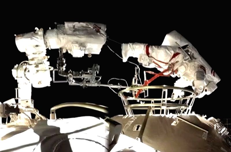 Shenzhou 12 spacewalker Liu Boming positions himself to mount the end of a robotic arm outside of China's space station.  Credit: CCTV news