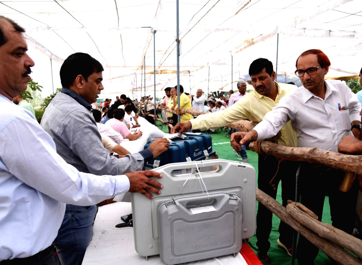 Sonipat: Polling officials collecting the Electronic Voting Machine (EVMs) and other necessary inputs required for the Haryana Assembly Election at a distributions centre in Sonipat on Oct 20, 2019. (Photo: IANS/PIB)
