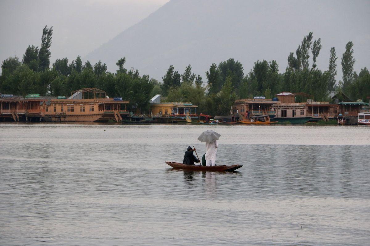Srinagar: A man enjoys boat ride in the Dal Lake amidst rains in Srinagar on July 18, 2019.