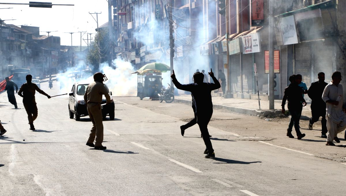 Srinagar: Police resorts to tear gas shelling and cane charge to disperse mourners who violated prohibitory orders and took out Muharram procession, in Srinagar on Sept 19, 2018.