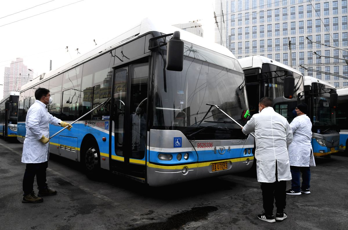Staff members disinfect a bus at a bus station in Beijing