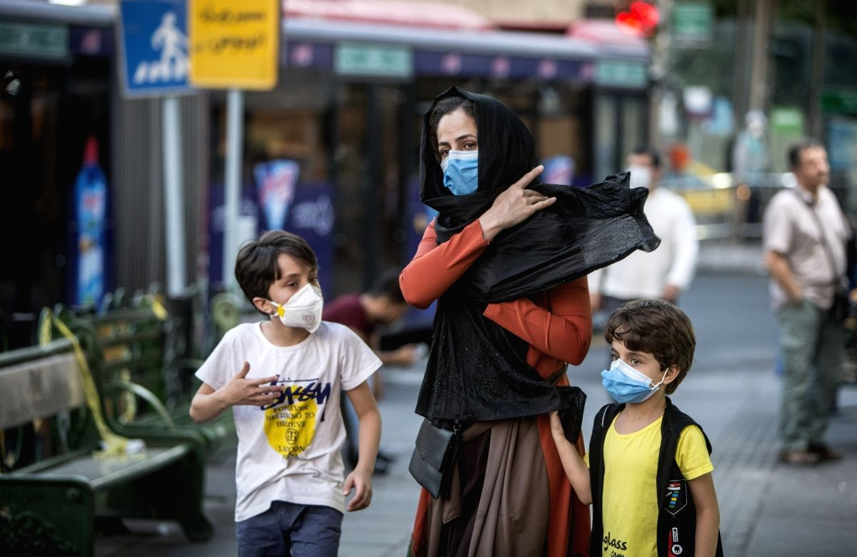 TEHRAN (Xinhua) -- Children wearing face masks walk with their mother at a street in Tehran, Iran (Photo: Xinhua/IANS)