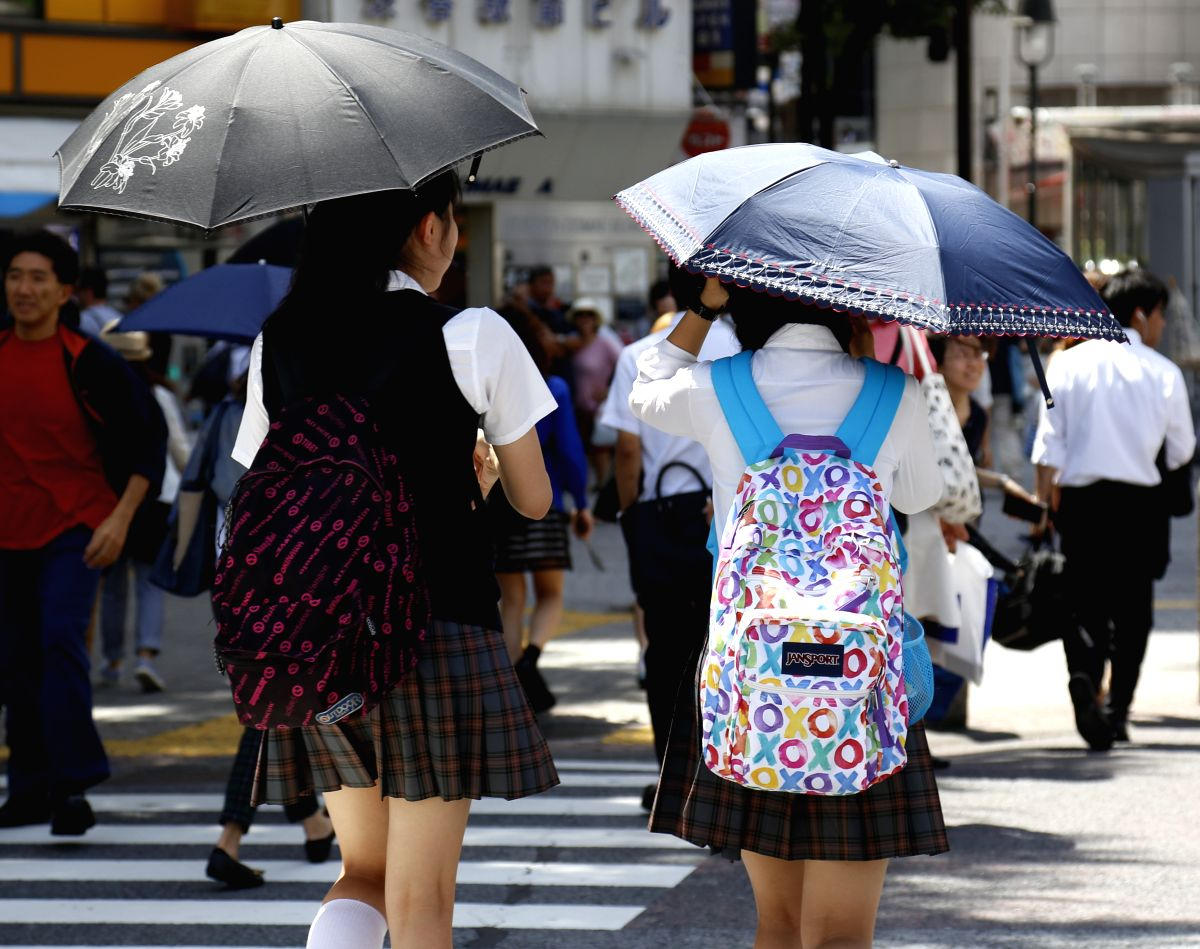 TOKYO, July 13, 2015 (Xinhua) -- Students carry umbrellas to block strong sunlight in Tokyo, Japan, July 13, 2015. Hot weather is observed in Japan Monday. (Xinhua/Stringer/IANS)