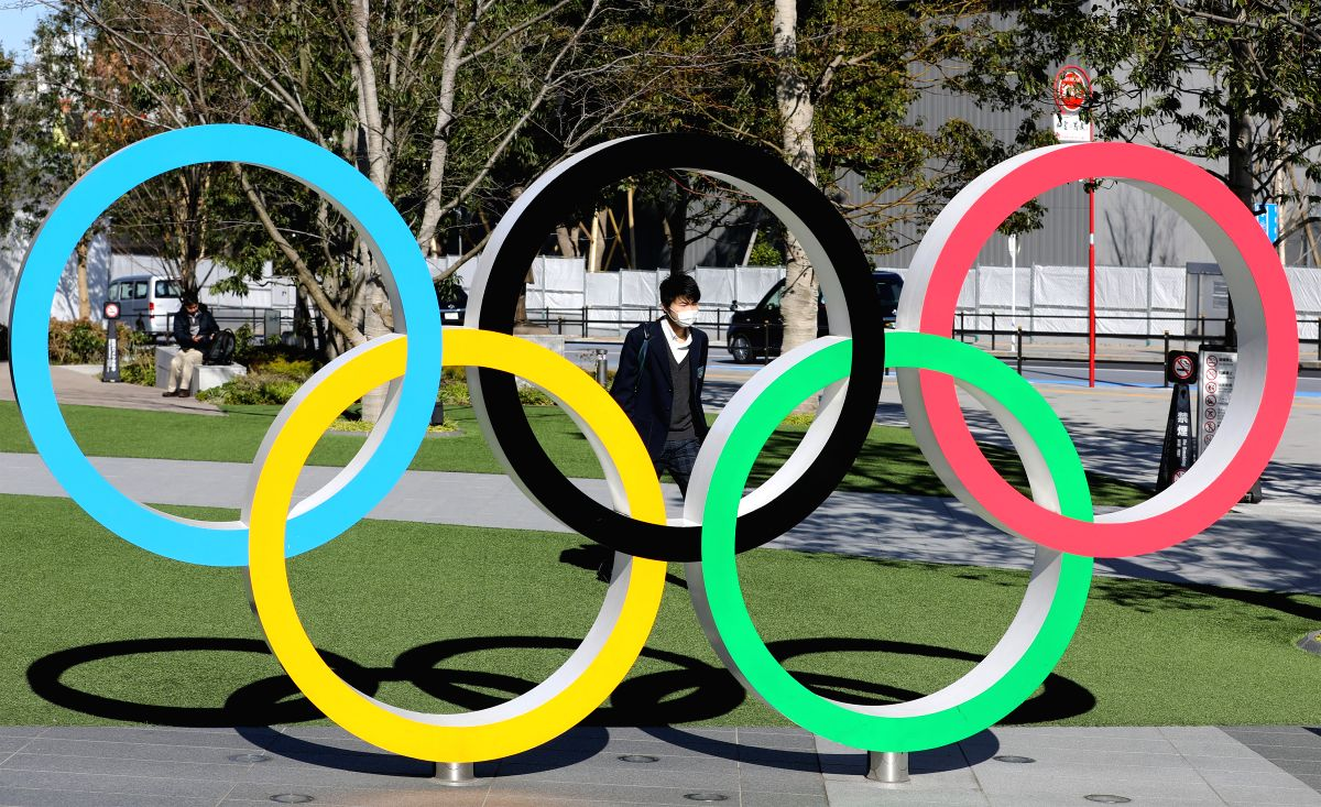 TOKYO, March 13, 2020 (Xinhua) -- A pedestrian wearing mask walks past the Olympic rings in Tokyo, Japan, March 12, 2020. Japan's health ministry and local governments said Friday the number of COVID-19 infections rose by 21 to 697 cases in Japan as