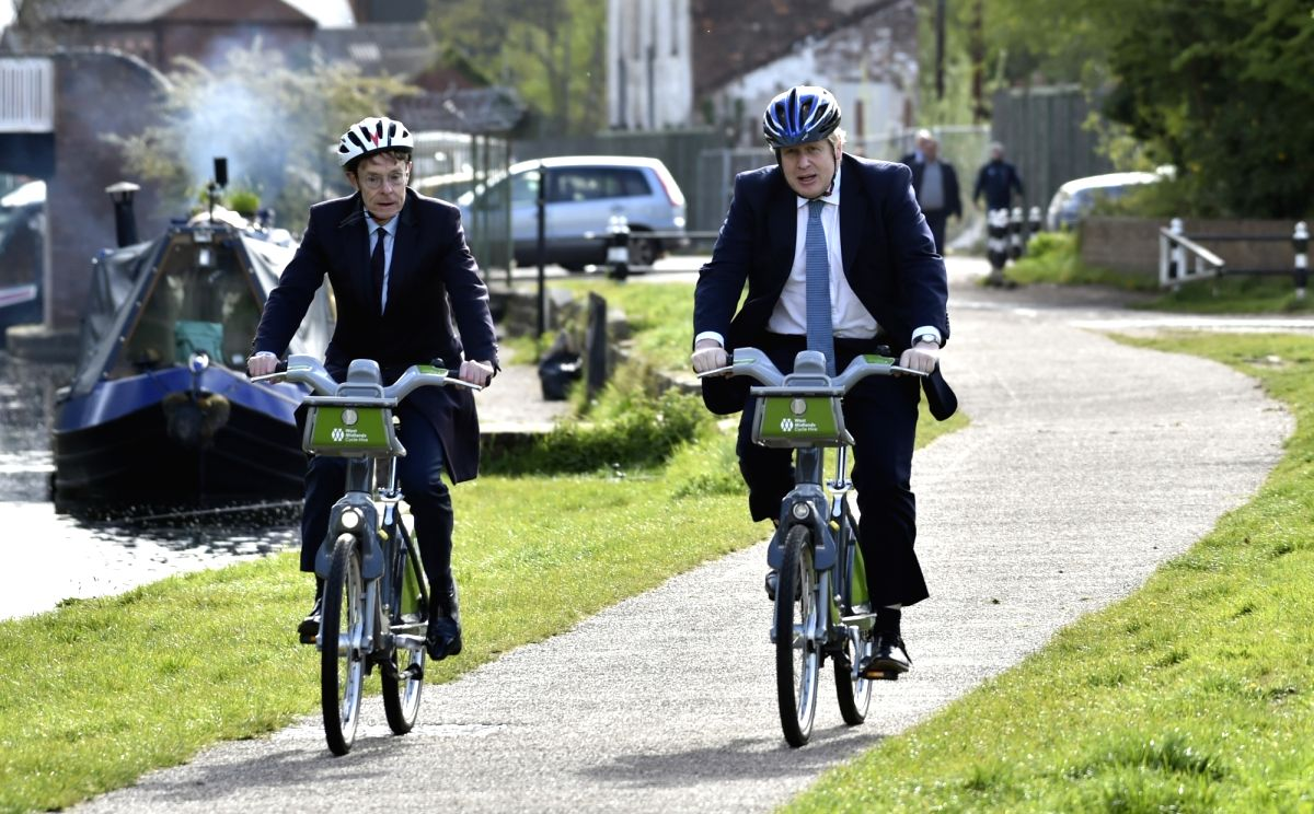 UK Prime Minister Boris Johnson (R) and mayor for West Midlands Andy Street ride bikes along the towpath of the Stourbridge canal during the local election campaign trail. Photo: Rui Vieira/PA Wire/dpa/IANS