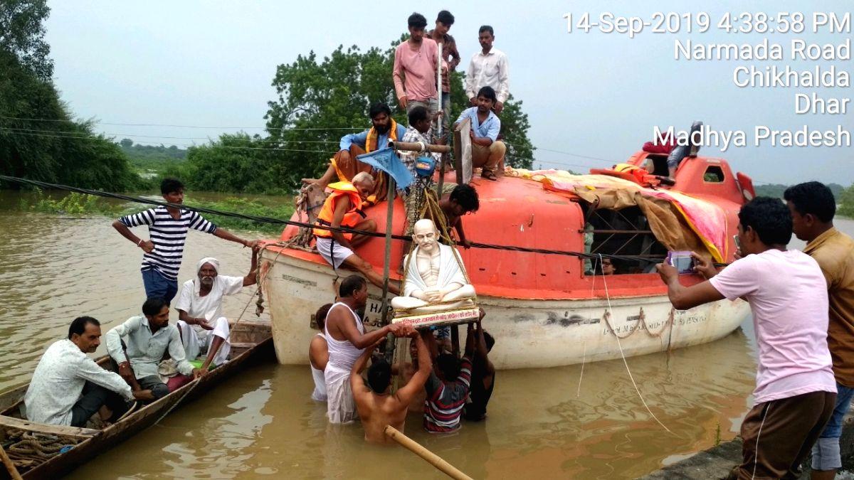 Villagers rescue the statute of Mahatma Gandhi in the flood affected Chikhalda village of Madhya Pradesh.