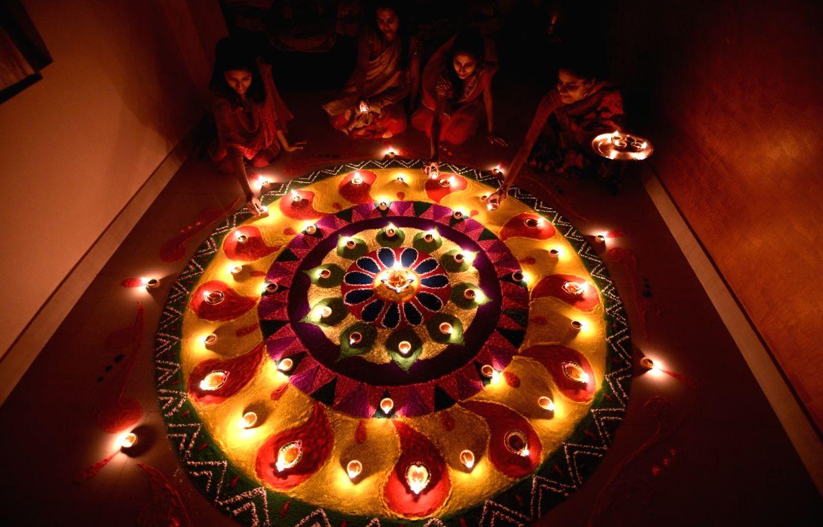 Women light earthen lamps on Diwali