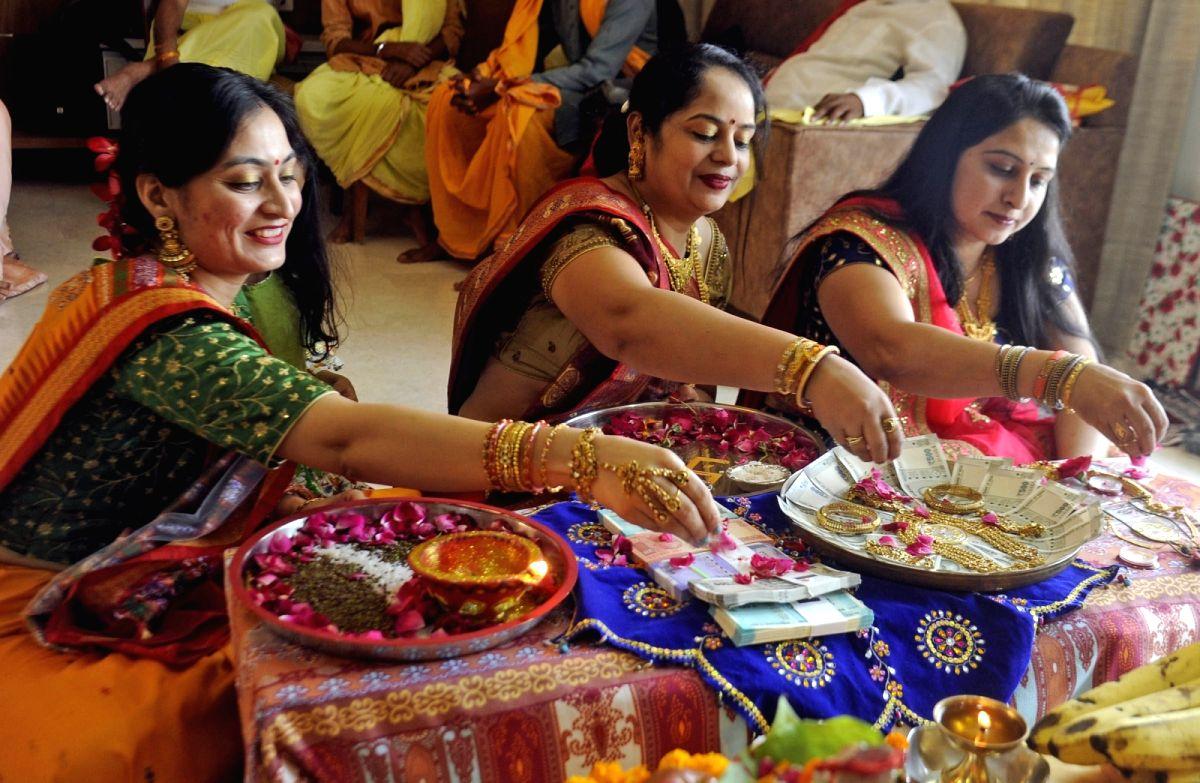 Women perform Dhanteras Puja