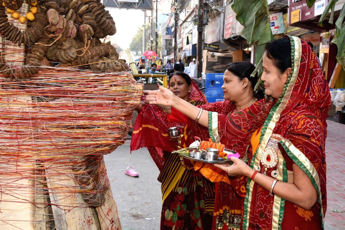 Women perform rituals around 'Holika' ahead of Holika Dahan on the eve of Holi