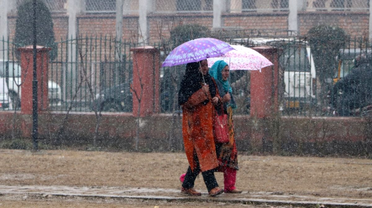 Women shield themselves with umbrellas during snowfall in Srinagar, on Jan 30, 2019.