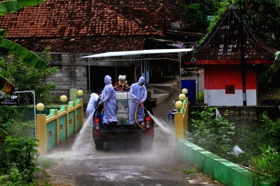 Workers wearing protective suits spray disinfectant to a residential area at Sleman district in Yogyakarta, Indonesia, May 29, 2021. (Photo by Joni/Xinhua/IANS)
