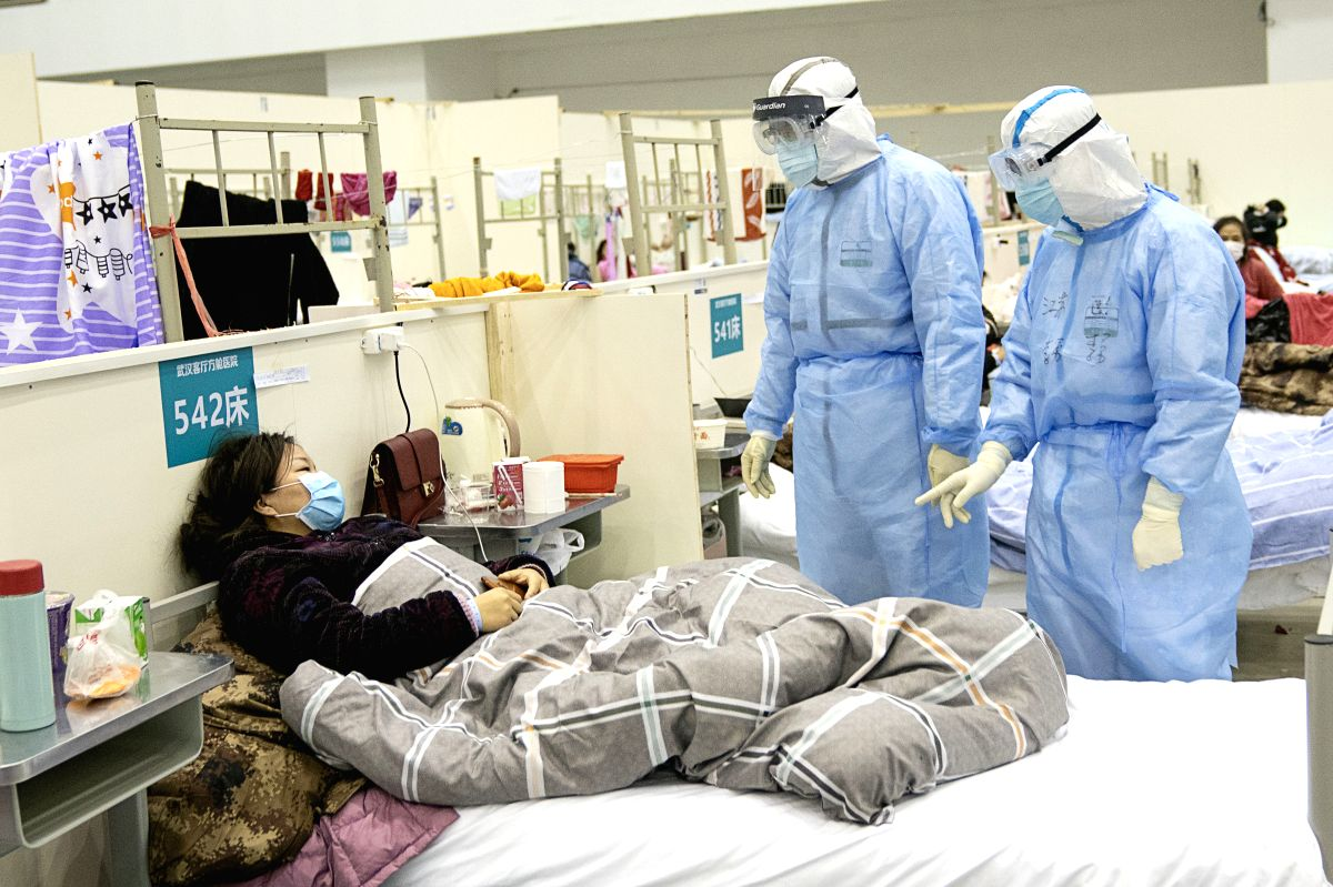 """WUHAN, Feb. 10, 2020 (Xinhua) -- Medical staff check a patient's condition at a temporary hospital converted from """"Wuhan Livingroom"""" in Wuhan, central China's Hubei Province, Feb. 10, 2020. In face of the outbreak of the novel coronavirus pneumonia e"""