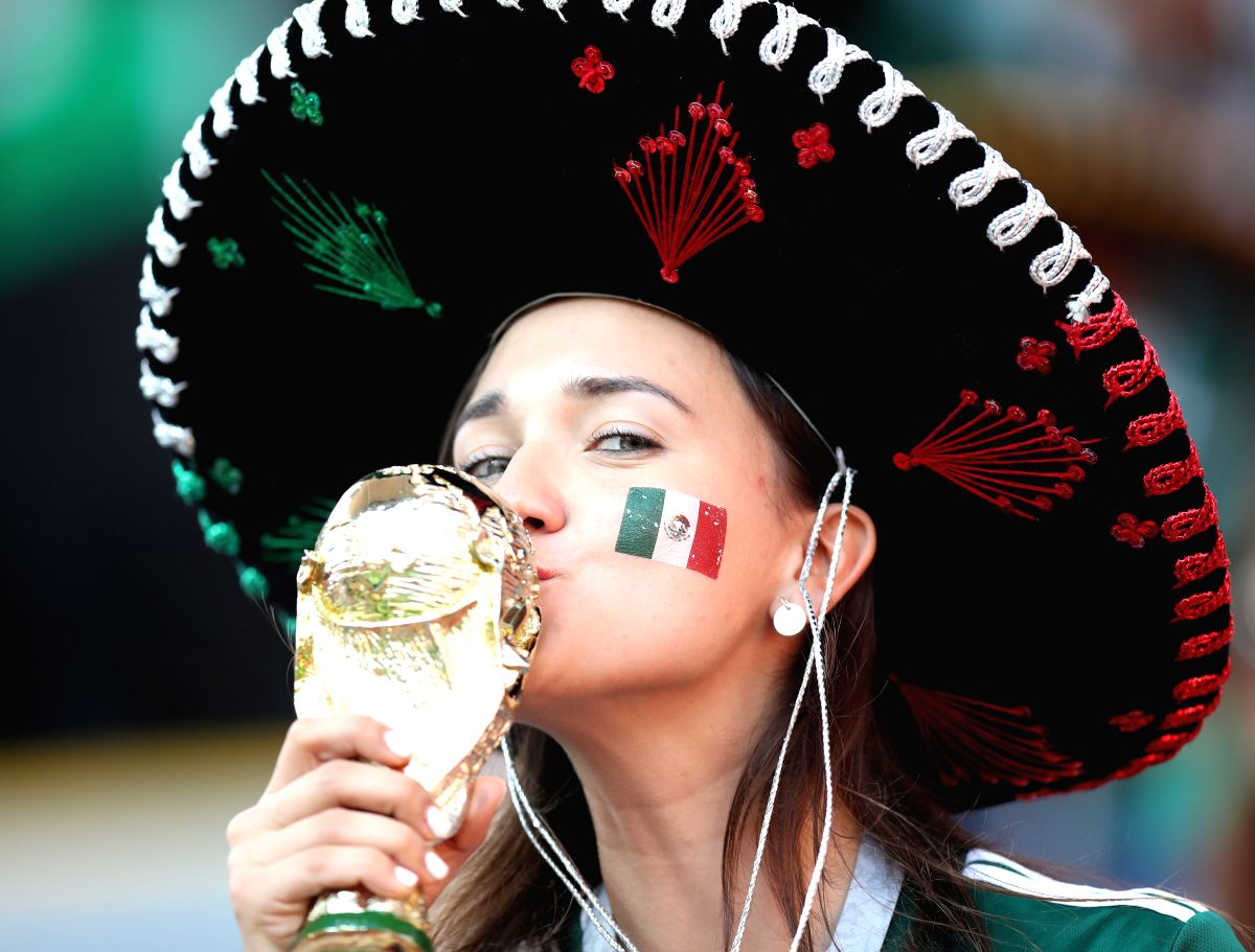A fan of Mexico kisses a replica of the World Cup