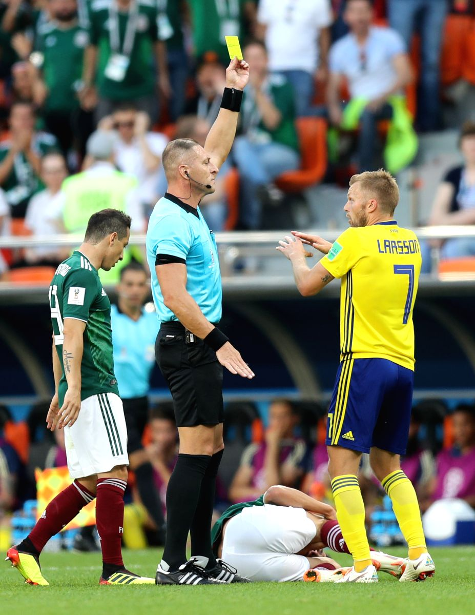 Referree stands his ground as he gives a yellow card to Sebastian Larsson