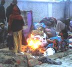 Allahabad: Homeless people warm themselves around a fire