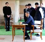 New Delhi: Obama signs the visitors book at Rajghat