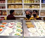 A confectioner sells sweets with symbols of political parties ahead of State Assembly elections, in Kolkata