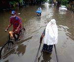 A hand rickshaw puller wades through a water logged street during heavy rainfall in Kolkata.